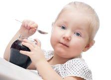 Κορίτσι που τρώει τη μαρμελάδα. Πέρα από το λευκό. Κινηματογράφηση σε πρώτο πλάνο. Στοκ Εικόνα