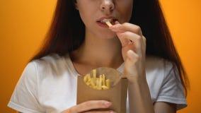 Κορίτσι που τρώει τις τηγανιτές πατάτες, που απολαμβάνουν το γρήγορο φαγητό, υψηλό γεύμα θερμίδας, κίνδυνος παχυσαρκίας φιλμ μικρού μήκους