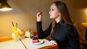Κορίτσι που τρώει το βακκίνιο cheescake στον καφέ από το βούλωμα επιδορπίων εσωτερικός Πρόσφατα συμπιεσμένος χυμός από πορτοκάλι  απόθεμα βίντεο