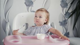 Κορίτσι που τρώει το γιαούρτι στην κουζίνα, λίγα τρόφιμα παιδιών μωρών, παιδί που τρώει με το κουτάλι απόθεμα βίντεο