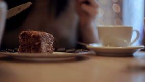 Κορίτσι που τρώει το κέικ και που πίνει τον καφέ στον καφέ φιλμ μικρού μήκους