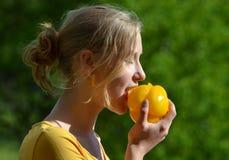 Κορίτσι που τρώει το κίτρινο peper Στοκ Εικόνες