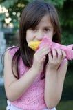Κορίτσι που τρώει το καλαμπόκι στο σπάδικα Στοκ εικόνα με δικαίωμα ελεύθερης χρήσης