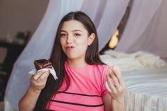 Κορίτσι που τρώει το νόστιμο browny κέικ με στην κρεβατοκάμαρα γλυκό επιδορπίων παλαιά επιχειρησιακού καφέ συμβάσεων διαμορφωμένη Στοκ φωτογραφίες με δικαίωμα ελεύθερης χρήσης