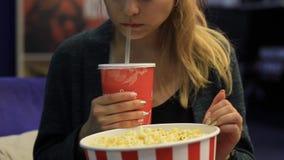 Κορίτσι που τρώει popcorn και που πίνει ένα ποτό φιλμ μικρού μήκους