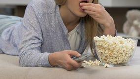 Κορίτσι που τρώει popcorn και που προσέχει τα τρυπώντας προγράμματα TV, τηλεοπτικός καταναλωτισμός απόθεμα βίντεο