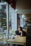 Κορίτσι που φαίνεται έξω παράθυρο στον καφέ Στοκ Εικόνα