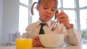 Κορίτσι που φορά τη σχολική στολή που τρώει τα δημητριακά προγευμάτων φιλμ μικρού μήκους