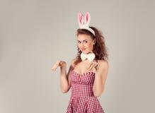 Κορίτσι που φορά το κοστούμι λαγουδάκι Πάσχας με τα αυγά στο καλάθι Στοκ Φωτογραφίες