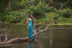 Κορίτσι που φορά το φόρεμα που στέκεται στον ποταμό κοντά στο δάσος Στοκ φωτογραφία με δικαίωμα ελεύθερης χρήσης