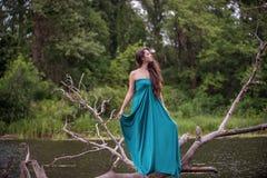Κορίτσι που φορά το φόρεμα που στέκεται στον ποταμό κοντά στο δάσος Στοκ φωτογραφίες με δικαίωμα ελεύθερης χρήσης