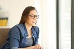 Κορίτσι που φορά eyeglasses που κοιτάζουν μέσω ενός παραθύρου Στοκ Φωτογραφίες