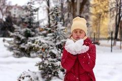 Κορίτσι που φυσά στο χιόνι στα χέρια του Στοκ εικόνες με δικαίωμα ελεύθερης χρήσης