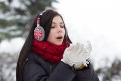 Κορίτσι που φυσά χνουδωτά snowflakes Στοκ Φωτογραφία