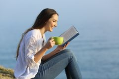Κορίτσι που χαλαρώνει διαβάζοντας ένα βιβλίο και πίνοντας τον καφέ υπαίθρια Στοκ Εικόνες