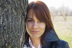 κορίτσι που χαμογελά πλησίον το δέντρο Στοκ εικόνα με δικαίωμα ελεύθερης χρήσης