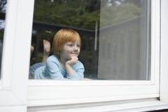 Κορίτσι που χαμογελά κοιτάζοντας έξω μέσω του παραθύρου γυαλιού Στοκ Φωτογραφία