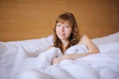 Κορίτσι που χαμογελά στο κρεβάτι Στοκ φωτογραφία με δικαίωμα ελεύθερης χρήσης