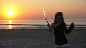Κορίτσι που χορεύει με ένα κερί πυροτεχνημάτων στο λυκόφως στην αμμώδη παραλία στο ηλιοβασίλεμα φιλμ μικρού μήκους