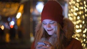 Κορίτσι που χρησιμοποιεί ένα τηλέφωνο κυττάρων υπαίθρια τη νύχτα φιλμ μικρού μήκους