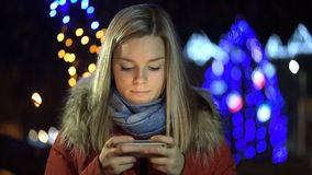 Κορίτσι που χρησιμοποιεί ένα τηλέφωνο κυττάρων υπαίθρια τη νύχτα απόθεμα βίντεο