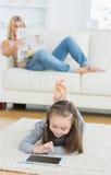 Κορίτσι που χρησιμοποιεί την εφημερίδα ανάγνωσης ταμπλετών και μητέρων Στοκ Εικόνα