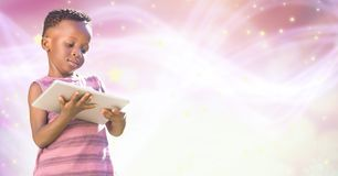 Κορίτσι που χρησιμοποιεί την ψηφιακή ταμπλέτα πέρα από το ροζ που καίγεται bokeh Στοκ φωτογραφίες με δικαίωμα ελεύθερης χρήσης