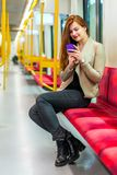 Κορίτσι που χρησιμοποιεί το κινητό τηλέφωνο μέσα στο υπόγειο τρένο Στοκ Εικόνες