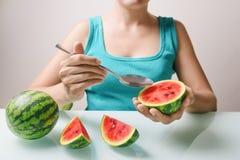 Κορίτσι που χρησιμοποιεί το κουτάλι για την κατανάλωση των ώριμων juicy κόκκινων μικρών καρπουζιών Στοκ Φωτογραφίες