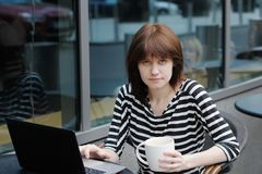 Κορίτσι που χρησιμοποιεί το lap-top σε έναν υπαίθριο καφέ Στοκ Εικόνα