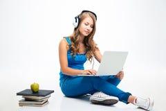 Κορίτσι που χρησιμοποιεί το lap-top στα ακουστικά στο πάτωμα στοκ εικόνα