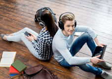 Κορίτσι που χρησιμοποιούν ένα smartphone και αγόρι που χρησιμοποιούν μια ταμπλέτα στα ακουστικά που ακούνε τη μουσική Στοκ φωτογραφίες με δικαίωμα ελεύθερης χρήσης
