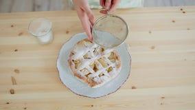 κορίτσι που ψεκάζει τη σκόνη άσπρης ζάχαρης σε ένα κέικ φιλμ μικρού μήκους