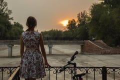 Κορίτσι, ποδήλατο και ηλιοβασίλεμα Στοκ Εικόνες