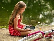 Κορίτσι ποδηλάτων στο πάρκο Τα παιδιά προσέχουν το PC ταμπλετών Στοκ Εικόνες
