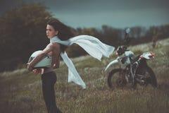 Κορίτσι ποδηλατών δίπλα σε μια μοτοσικλέτα Στοκ φωτογραφία με δικαίωμα ελεύθερης χρήσης