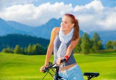 Κορίτσι ποδηλατών στα βουνά Στοκ Εικόνες