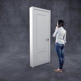 Κορίτσι πριν από μια πόρτα Στοκ Φωτογραφίες
