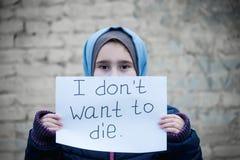 Κορίτσι προσφύγων με μια επιγραφή σε ένα άσπρο φύλλο στοκ εικόνες με δικαίωμα ελεύθερης χρήσης