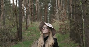 Κορίτσι προσώπου σε ένα καπέλο στα ξύλα φιλμ μικρού μήκους