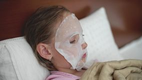 Κορίτσι προ-εφήβων με την ενυδατική μάσκα προσώπου υφασμάτων στο πρόσωπο που βάζει στο κρεβάτι απόθεμα βίντεο