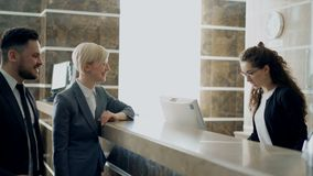 Κορίτσι ρεσεψιονίστ που μιλά με τους προσεγγισμένους φιλοξενουμένους επιχειρηματιών και επιχειρηματιών για την είσοδο στο ξενοδοχ απόθεμα βίντεο