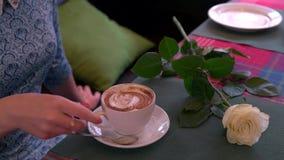 Κορίτσι σε έναν καφέ κατανάλωσης καφέδων φιλμ μικρού μήκους