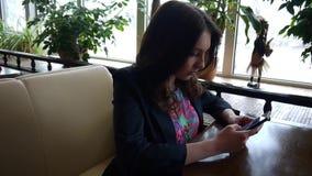 Κορίτσι σε έναν καφέ που εξετάζει το τηλέφωνο απόθεμα βίντεο