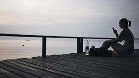 Κορίτσι σε έναν λιμενοβραχίονα με ένα smartphone σε ένα ταξίδι φιλμ μικρού μήκους