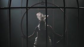 Κορίτσι σε έναν σπάγγο που περιστρέφει σε μια στεφάνη σε ένα κλουβί στο σκοτεινό στούντιο Μαύρο υπόβαθρο καπνού σκιαγραφία κίνηση απόθεμα βίντεο