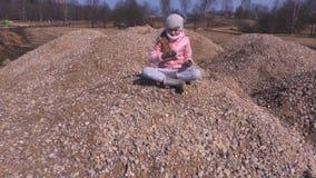 Κορίτσι σε έναν σωρό αμμοχάλικου φιλμ μικρού μήκους