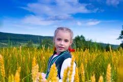 Κορίτσι σε έναν τομέα του σίτου σε ένα τοπίο Στοκ Φωτογραφία