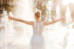 Κορίτσι σε έναν ψεκασμό του νερού σε μια πηγή στοκ εικόνες