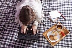 Κορίτσι σε ένα άσπρο μάλλινο πουλόβερ που λειτουργεί σε ένα lap-top δίσκος με ένα φλυτζάνι του τσαγιού και ένα πιάτο με τα μπισκό Στοκ Εικόνες